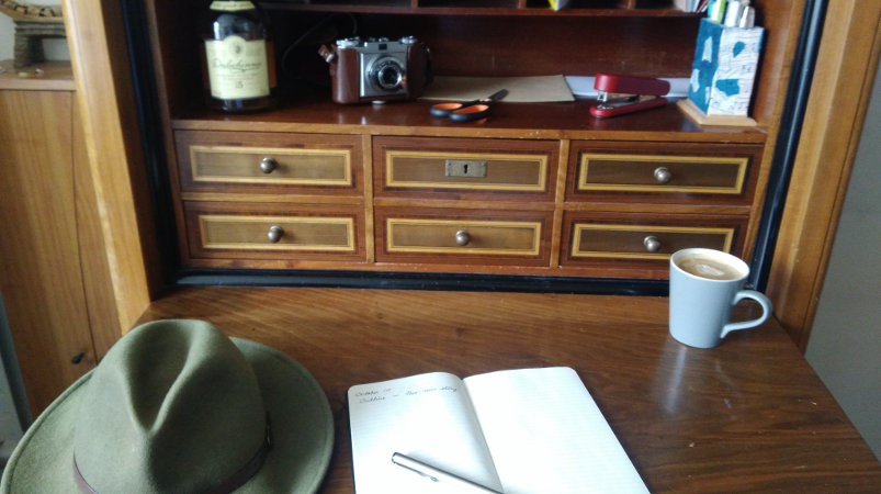 Hat, notebook, coffee cup on desk